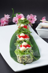 Sushi roll in tempura with salad chuka with red tobiko