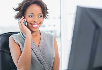 Smiling businesswoman talking on phone while looking at computer