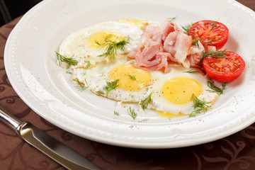 fried eggs with bacon and vegetables