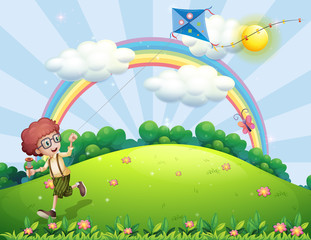 A boy playing with his kite at the hilltop with a rainbow