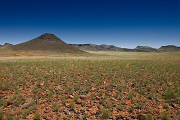 Landschaft mit Bergen und grüner Ebene in Namibia