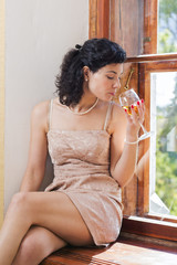 Woman sit on sill and smells wine