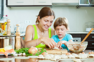 woman with child cooking fish pelmeni (pelmeni), today together