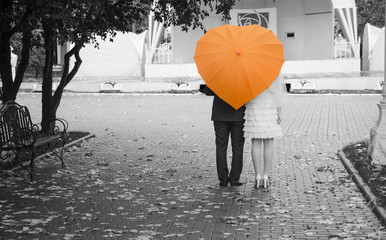 Newlyweds under an orange umbrella
