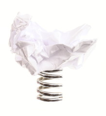 Crumpled paper ball on metal spring isolated
