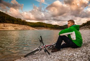 Young man cyclist relaxing near the mountain lake