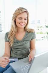 Woman looking at her laptop screen while holding her credit card