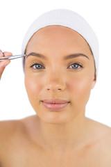 Pretty woman wearing headband using tweezers