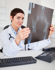 Serious female doctor holding a set of X-ray