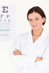 Female optician with crossed arms and eye test