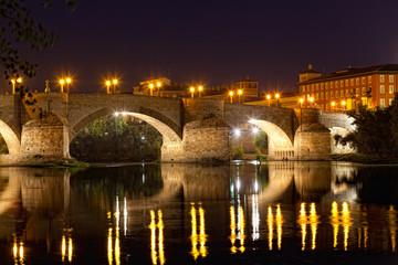 old stone bridge through the river Ebro in Zaragoza, Spain