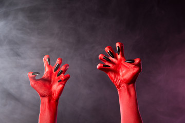Spooky red devil hands with black glossy nails