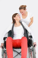 Krankenpflegerin unterstützt Rollstuhlfahrerin