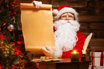 Santa Claus with gift boxes in wooden house interior