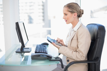 Side view of cheerful blonde businesswoman using calculator