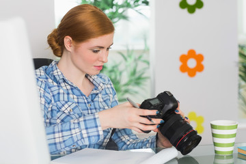Focused photographer sitting at her desk looking at her camera