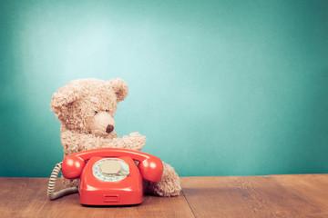 Retro red telephone and Teddy Bear near mint green wall