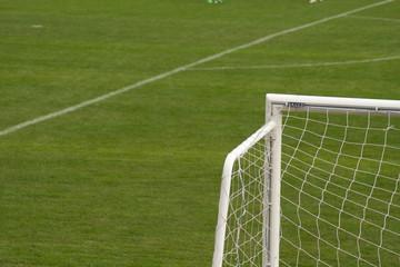 Porta da calcio con sfondo campo di gioco