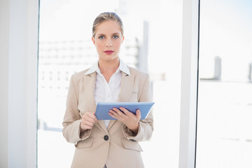 Serious blonde businesswoman using tablet pc