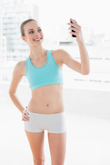 Sporty attractive woman smiling at smartphone