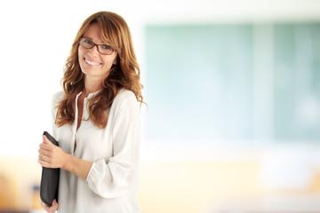 Smiling teacher in front of blackboard