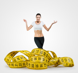 Fit young woman with a large measuring tape