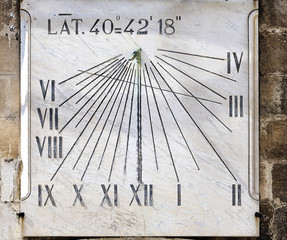 Ancient sundial on the wall a bell tower - Italy