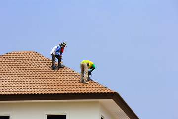 Workers   repair  concrete  roof  tile
