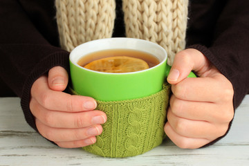 Cup with knitted thing on it in female hands close up