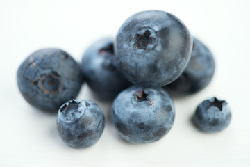 Macro shot of blueberries over white wooden background