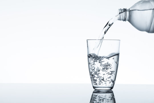 water flowing from plastic bottle into a glass