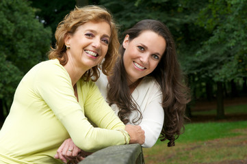 Portrait of a happy mother and daughter smiling outdoors