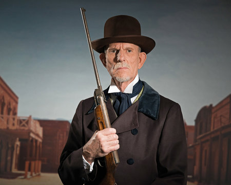 Senior western man wearing a brown hat and coat holding rifle. S