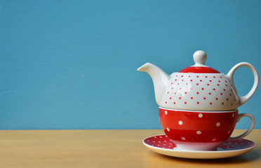 Red polka dot kettle on wooden