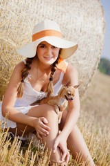 Pretty young woman in a field with your puppy chihuahua