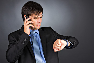 Young businessman talking on phone while looking at his watch