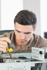 Handsome focused computer engineer repairing open computer