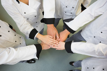 Five chefs joining hands in a circle