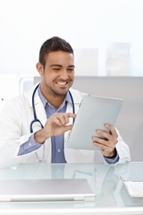 Happy doctor with tablet