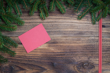 Pine tree with red ribbon on old wooden background