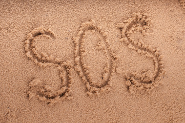 SOS on the beach sand at the sea.