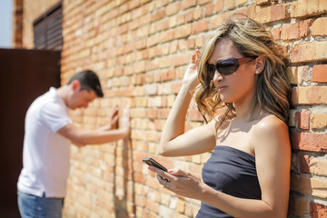Angry woman looking phone and man posing on wall