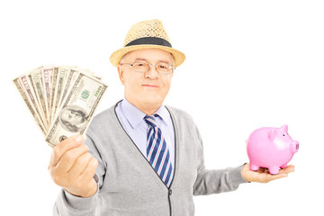Mature gentleman holding a piggy bank and US dollars