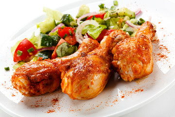 Grilled chicken legs and vegetables on white background