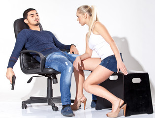 blond girl looking at man sitting on chair with gun