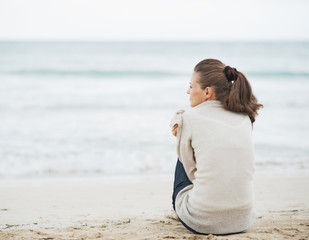 Young woman wrapping in sweater while sitting on lonely beach