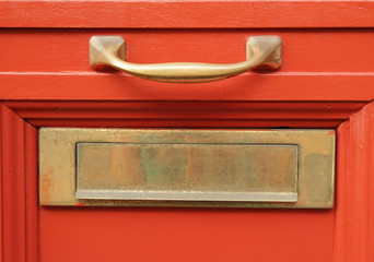 brass mailbox slot  on vivid red door