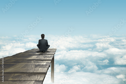 Wall mural businessman sitting on pier