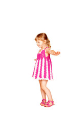 Happy little girl in knitted pink dress dancing.