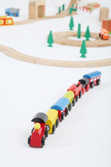 Toy train with cars and wooden toy railway with spruces
